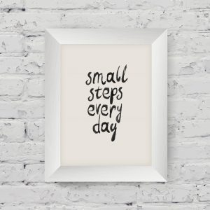 """Motivational poster """"small steps every day"""" in the art wooden frame on on white brick wall"""